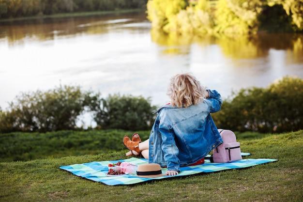 Blonde vrouw zit op de plaid met picknick aan de oever van de rivier. samen genieten van het leven, een fijn weekend of vakantie hebben.