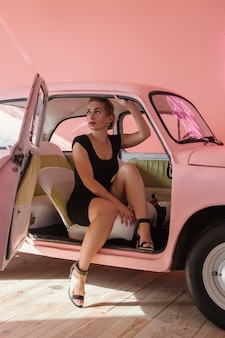 Blonde vrouw zitten in roze auto. conceptuele mode-opname. vintage stijl fotografie.