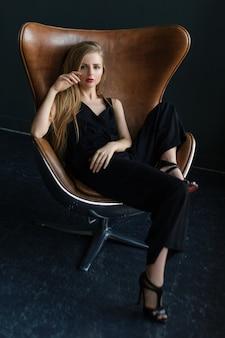 Blonde vrouw zittend in een stoel in art nouveaustijl.