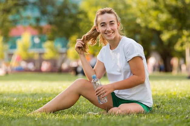 Blonde vrouw zittend op gras in sportkleding