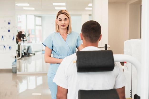 Blonde vrouwelijke arts die geduldige voorwaarde controleert
