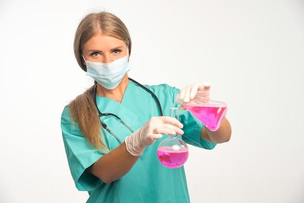 Blonde vrouwelijke arts die gezichtsmasker draagt en chemicaliën uit de ene kolf naar de andere brengt.