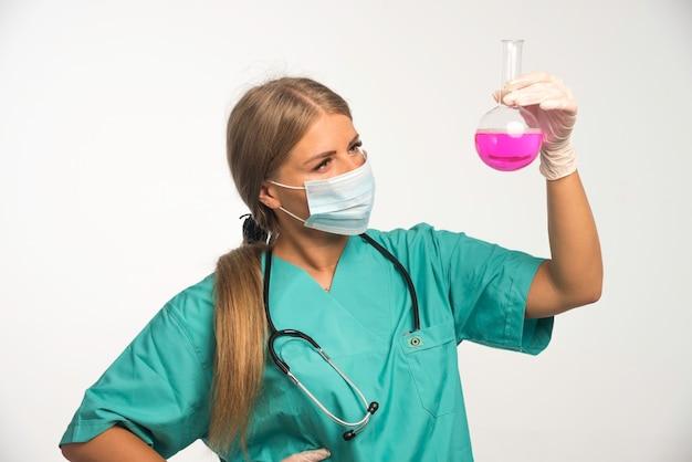 Blonde vrouwelijke arts die gezichtsmasker draagt en chemische kolf bekijkt.