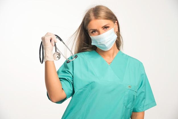 Blonde vrouwelijke arts die gezichtsmasker draagt en een stethoscoop houdt.