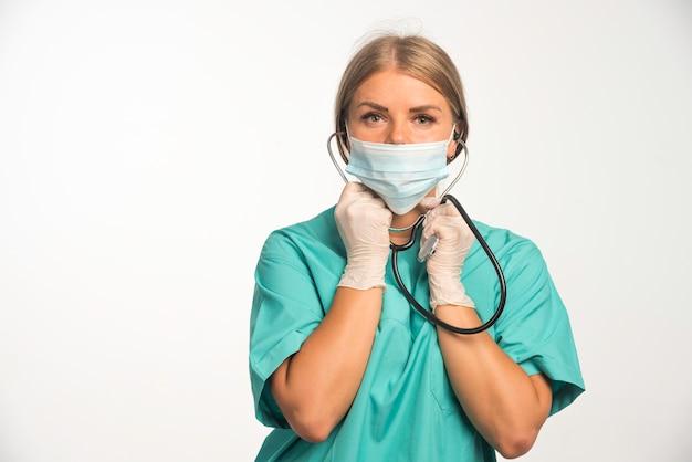 Blonde vrouwelijke arts die gezichtsmasker draagt en stethoscoop aan haar oren zet.