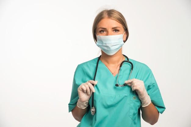 Blonde vrouwelijke arts die gezichtsmasker draagt en stethoscoop om haar hals zet