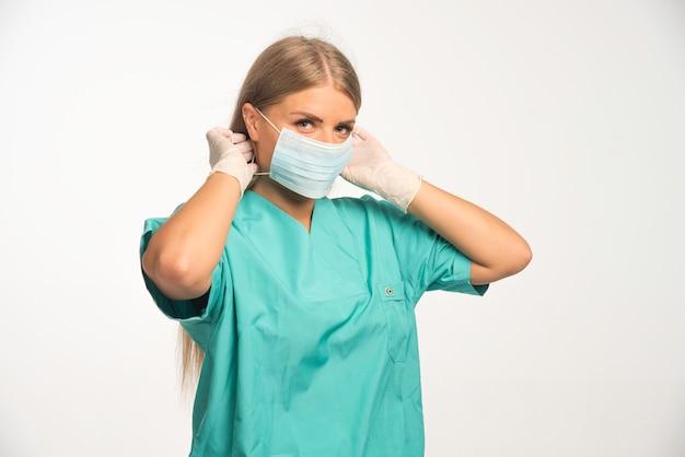 Blonde vrouwelijke arts die gezichtsmasker draagt.