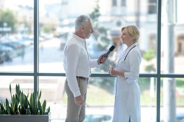 Blonde vrouwelijke arts die in microfoon spreekt, grijsharige mannelijke journalistvragen beantwoordt