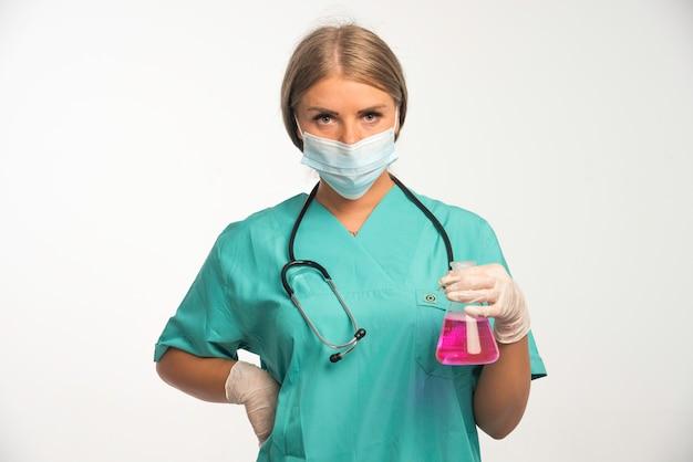 Blonde vrouwelijke arts in blauw uniform met een stethoscoop in de nek die gezichtsmasker draagt en een chemische kolf vasthoudt.