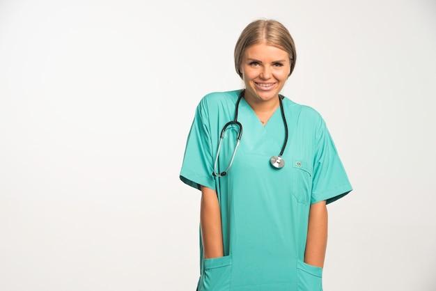 Blonde vrouwelijke arts in blauw uniform met een stethoscoop in de nek.