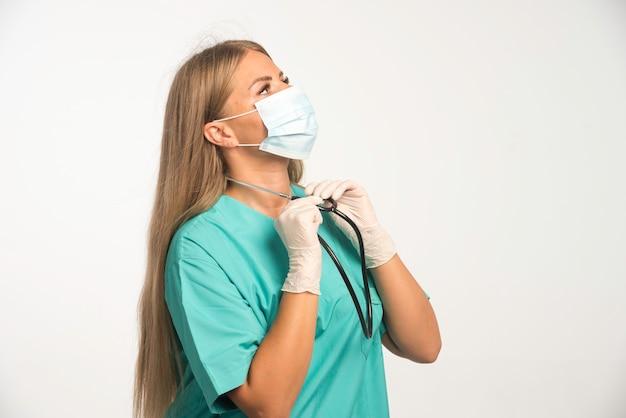 Blonde vrouwelijke arts in gezichtsmasker die stethoscoop draagt.