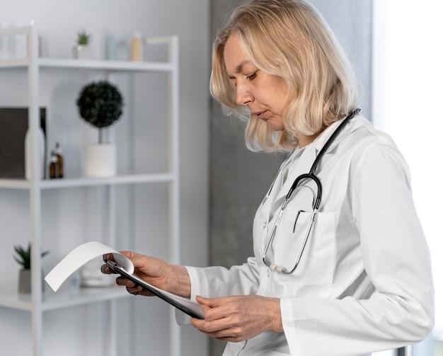 Blonde vrouwelijke arts in haar kantoor