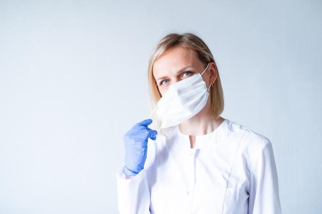 Blonde vrouwelijke artsenchirurg die in witte eenvormige, beschermende blauwe handschoenen op medisch masker over grijs zetten. gezondheidszorg, blijf thuis. copyspace