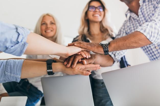 Blonde vrouwelijke beambte met glimlach opzoeken terwijl hand in hand met collega's. binnenportret van vrienden klaar om gezamenlijk werkproject te starten.
