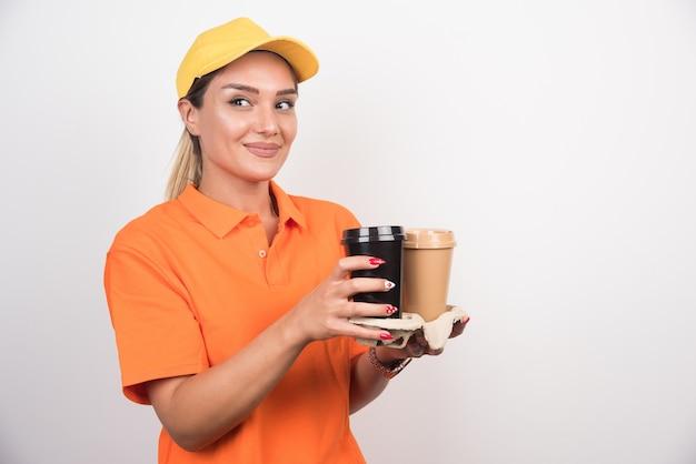 Blonde vrouwelijke koerier die kant bekijkt terwijl twee kopjes koffie vasthoudt.