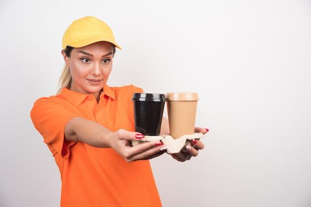 Blonde vrouwelijke koerier die twee kopjes koffie houdt.