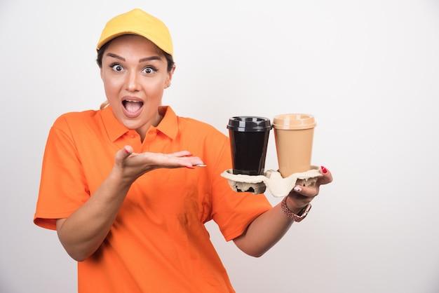 Blonde vrouwelijke koerier wijzend op twee kopjes koffie.
