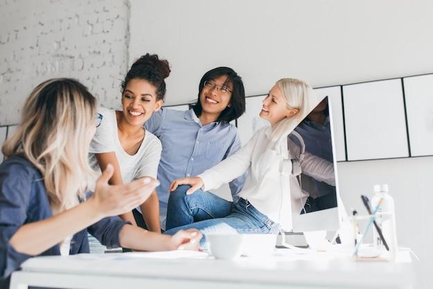 Blonde vrouwelijke secretaresse grappig verhaal vertellen aan lachende collega's. indoor portret van glimlachende aziatische kantoormedewerker luisteren naar blonde vriend, staande naast de computer.