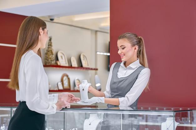 Blonde vrouwelijke werknemer in een grijs uniform met een ketting aan een vrouwelijke klant in een juwelier