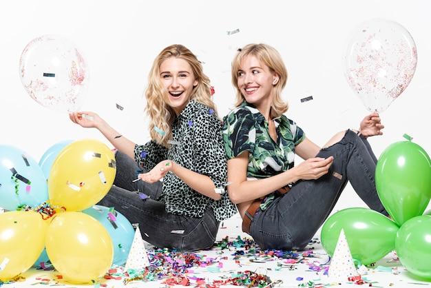 Blonde vrouwen omringd door confetti en ballonnen