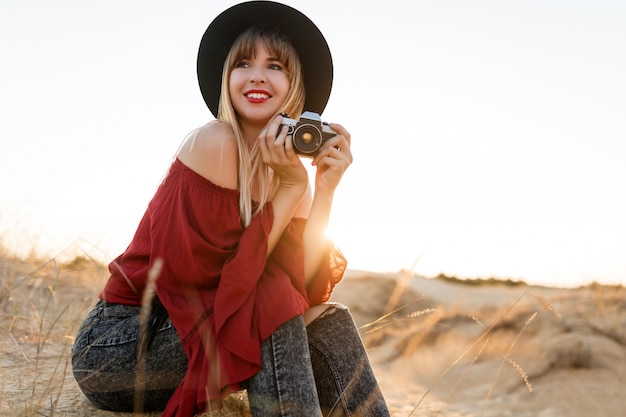 Blonde vrouwenfotograaf in boho-outfit