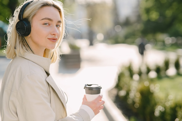 Blonde wandelingen in de zomer stad met een kopje koffie