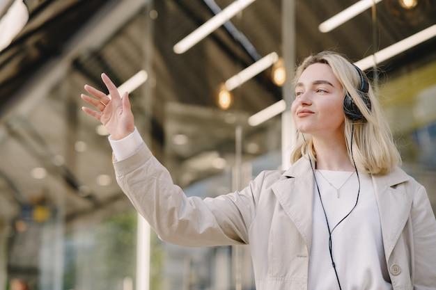 Blonde wandelingen in de zomer stad met koptelefoon