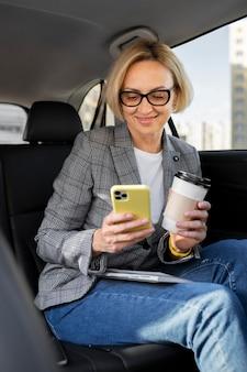 Blonde zakenvrouw die haar telefoon in haar auto controleert