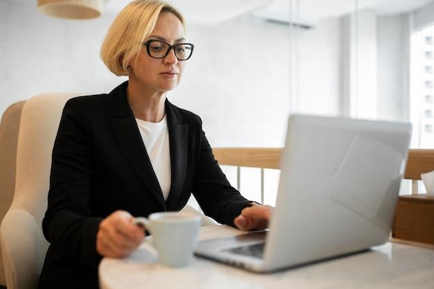 Blonde zakenvrouw die op haar laptop werkt
