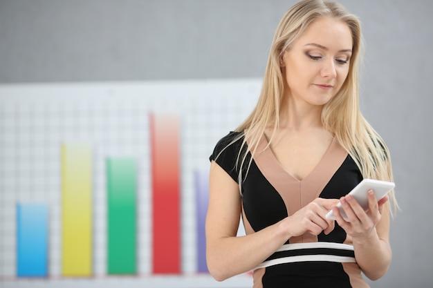 Blonde zakenvrouw gebruikt mobiele aanbieding voor handel op forex