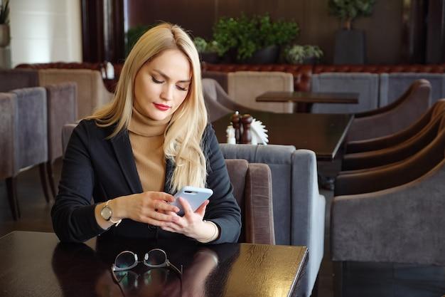 Blonde zakenvrouw in pak met telefoon zittend aan een tafel in een café