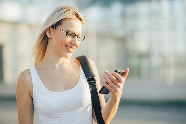 Blonde zakenvrouw leest een bericht op de telefoon
