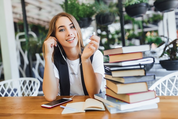 Blonde zakenvrouw met boeken op kantoor