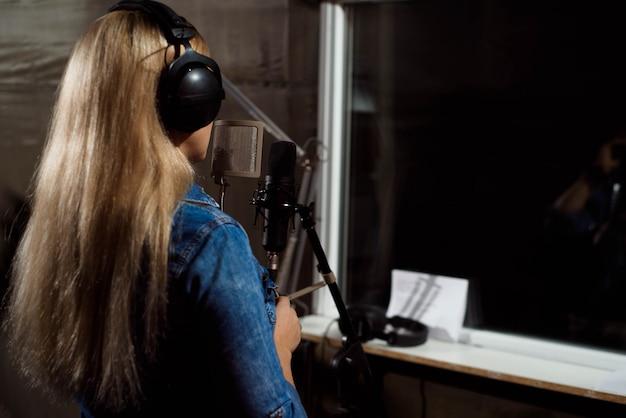 Blonde zingende vrouw in een opnamestudio