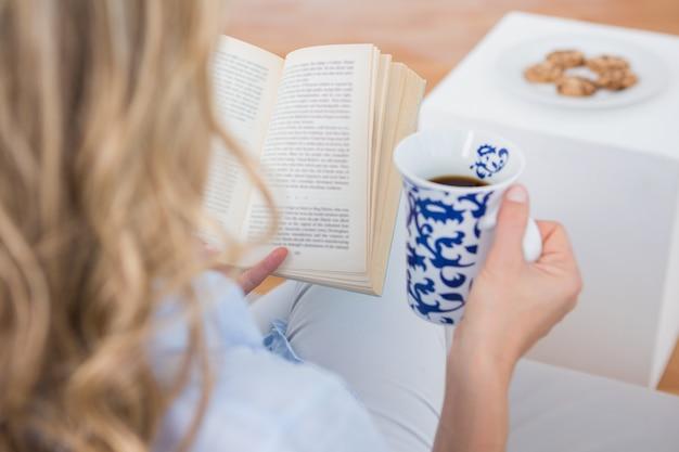 Blonde zittend op de bank lezen met een kopje koffie