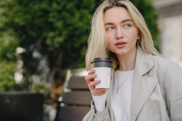 Blonde zittend op een bankje met een papieren beker