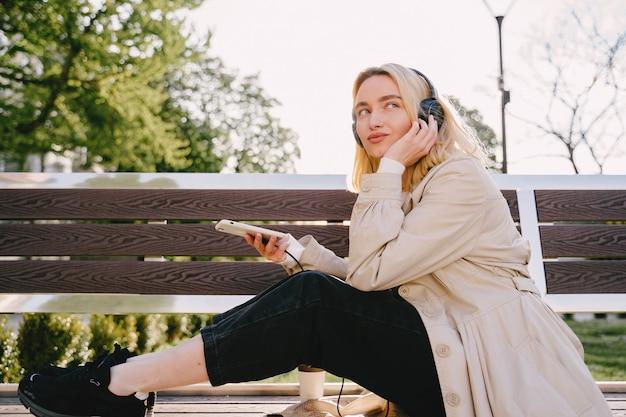 Blonde zittend op een bankje met mobiele telefoon