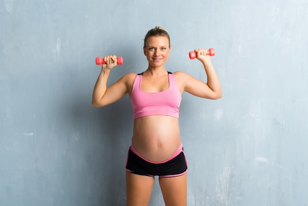 Blonde zwangere vrouw die sport doet die gewichtheffen maakt