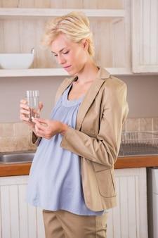 Blonde zwangerschap die een vitamine neemt