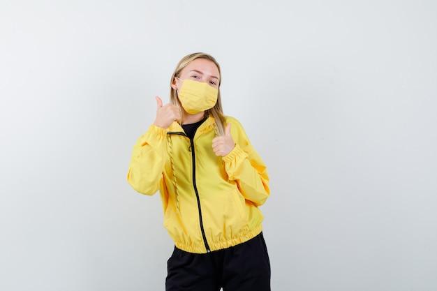 Blondedame in trainingspak, masker dat dubbele duimen toont en tevreden, vooraanzicht kijkt.