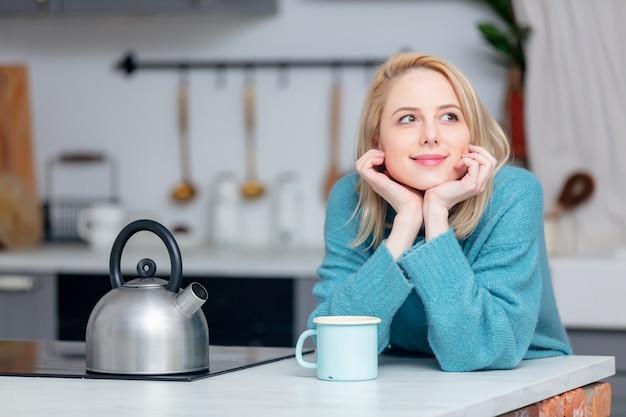 Blondedame met kop van koffie bij keuken