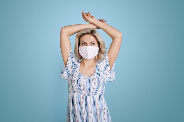 Blondedame met medisch masker op gezicht die een kleding draagt, stelt met handen hierboven op blauwe muur