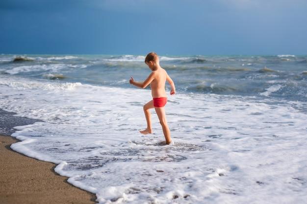 Blondejongen die en op het strand op blauwe overzeese kust in de zomervakantie in de dagtijd lopen springen.
