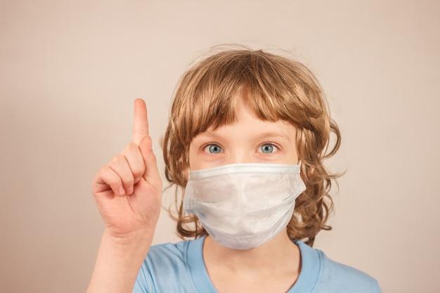 Blondejongen in blauwe t-shirt die medisch masker dragen en zijn vinger met exemplaarruimte benadrukken