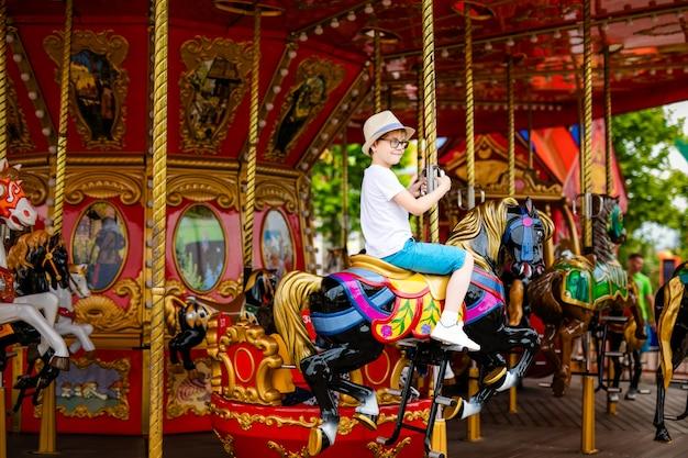 Blondejongen in de strohoed en grote glazen die kleurrijk paard in de draaimolencarrousel berijden.