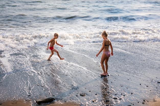 Blondejongen in rood zwempak en meisje die en pret op het strand op blauwe overzeese kust in de zomervakantie spelen in de dagtijd.