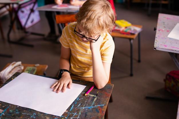 Blondejongen met glazen het trekken. groep basisschoolleerlingen in klaslokaal op kunstklasse