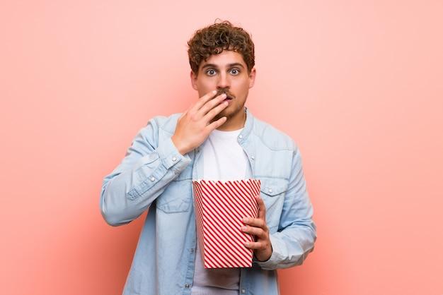 Blondeman over roze muur verrast en het eten van popcorns