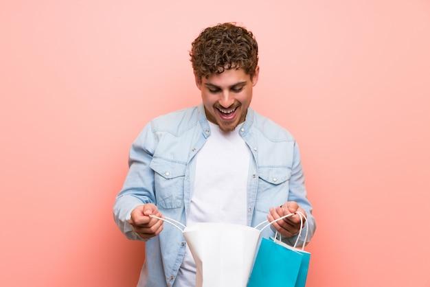 Blondeman over roze muur verrast terwijl hij veel boodschappentassen hield