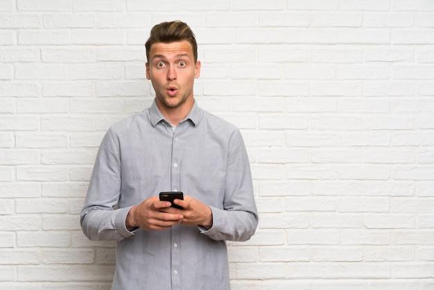 Blondeman over witte bakstenen muur verrast en een bericht verzenden